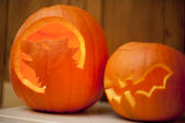 Two glowing Halloween pumpkin jack-o-lanterns with handmade decoration of a bat and howling wolf or werewolf