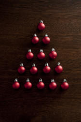 Christmas baubles tree shape with colorful red balls arranged in a triangle to resemble a modern Xmas tree over a dark background