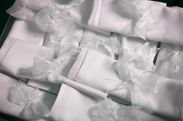 a pile of white linen napkins decorated with white lace ribbon for a wedding breakfast