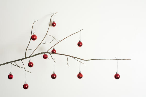 Modern decorated twig Christmas tree with a dried leafless branch decorated with colorful red baubles to celebrate the holiday, over white